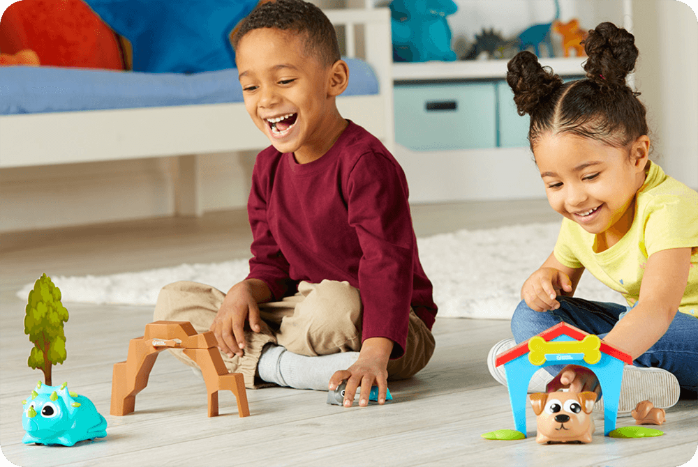 Two children playing with the Coding Critters products