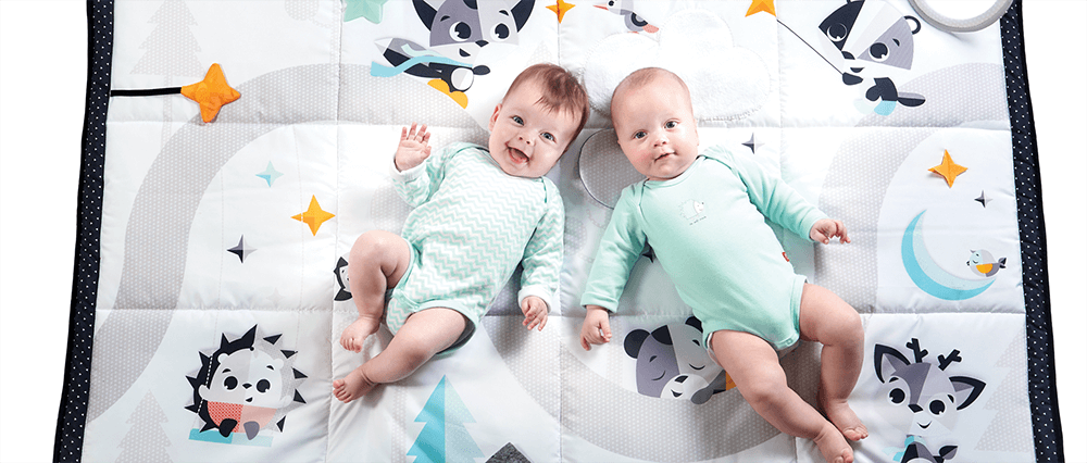 Two babies lying on the new black and white Magical Tales Collection mat