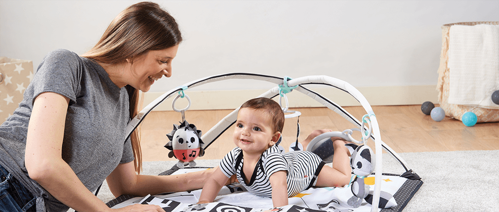 Mother interacting with her baby who is lying on the Gymini®