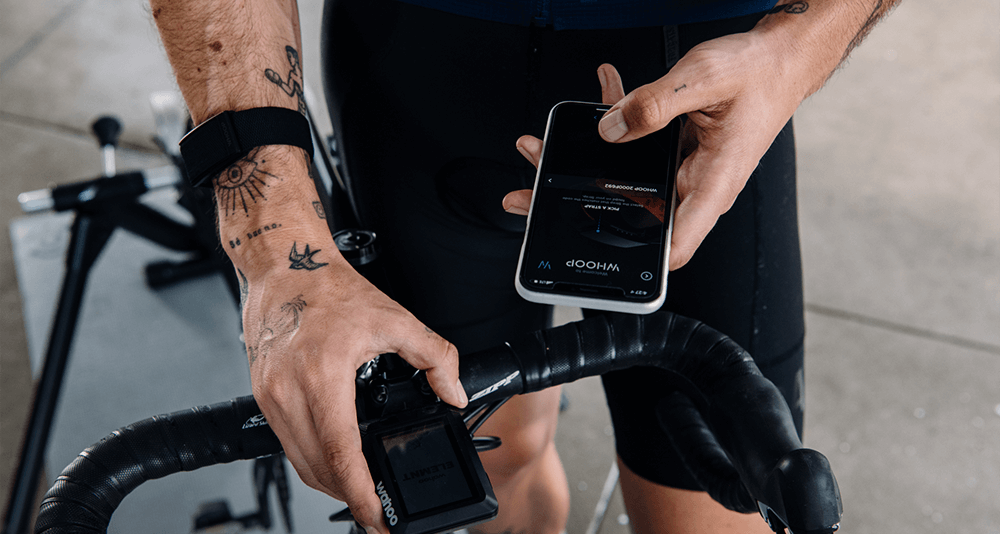 Close-up of cyclist using the Whoop app while stationary